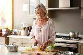 femmes plus cuisine une femme plus âgée dans la cuisine préparant le repas sain image