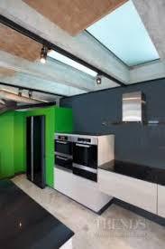 open plan kitchen with black glass splashback and poggenpohl