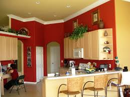 red wall theme and cream wooden kitchen cabinet connected by white