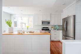 kitchen with white cabinets and wood countertops island with thin wood countertop transitional kitchen