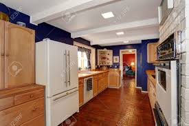 long kitchen room with royal walls light brown storage cabinets