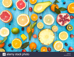 mix of colored fruits on white wooden background composition of