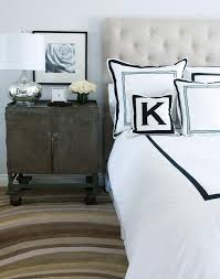 cream tufted headboard with black and white border bedding