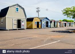 portable storage sheds for sale in the parking lot of a building