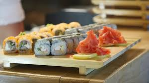 japanese restaurant cook at table cook puts plates with sushi and rolls on table and waiter takes them