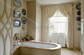 English Bathroom Collection Of Decorative Plates Above Wood Clad Bathtub With