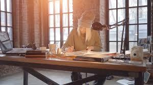 female fashion designer artist sitting at her desk drawing