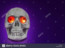 dark halloween background halloween human skull with eyes glowing red on dark purple