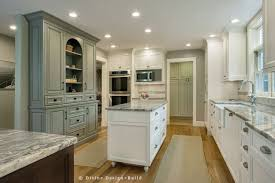 calm kitchen with olive painted color and wooden floor also