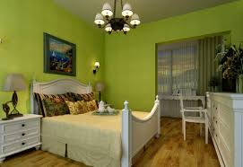 dark green walls in living room white bed striped blanket grey