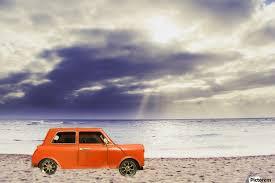 orange classic car on the sandy beach with beautiful sky and beach