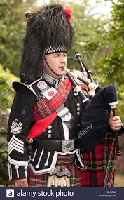 scottish piper with tartan kilt sporran busby bagpipes at the