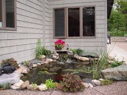 small ornemental backyard pond in corner space with stone surround