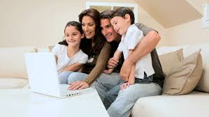 parents and daughters lying on bed shopping online with laptop at