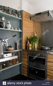 open shelving in kitchen with oven and extractor fan stock photo