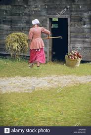 young woman walking away dressed in colonial times farm dress