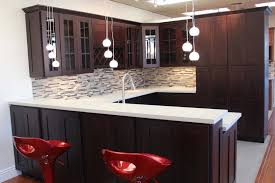 dark brown wooden kitchen cabinet and island with white quartz