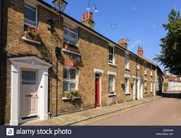 row of similar old terraced town houses along narrow street stock