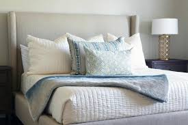 gray wingback bed with gray and blue pillows and gold quatrefoil