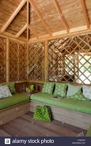 bamboo summer house with green upholstery and reflective wall
