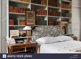 bookshelves above a bed with a marvic fabric headboard stock photo