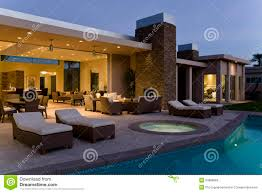 patio house house with sunloungers on patio by pool at dusk stock images