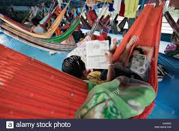 passangers sleep in hammocks in a river boat on amazon river peru