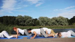 yoga class girls doing exercises cobra position on yoga mats