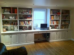 large white wooden bookshelves with white wooden doors plus study