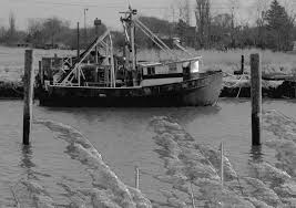 black and white photograph of an old fishing boat at rock harbor