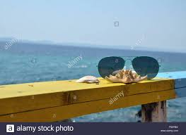 turquoise sunglasses sea star and shells on yellow wooden beach