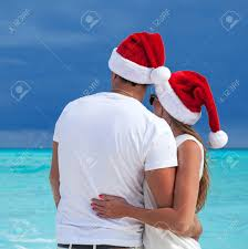 happy couple in santa hats looking to the seascape hugging and