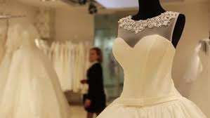 shop wedding dress up of dummy with wedding dress shop assistant is helping