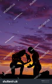 silhouette cowgirl kneeling down cowboy leaning stock photo
