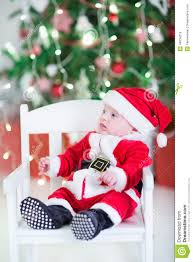 funny newborn baby boy in santa under under christmas tree