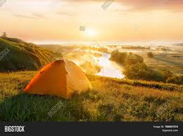 Sunset Orange by View Of Tourist Tent On Green Meadow At Sunrise Or Sunset Camping