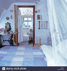 Attic Bedroom by White Voile Drapes And Blue Patchwork Quilt On Bed In Attic