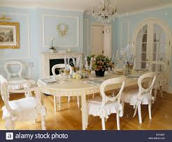 long cream oval table and cream chairs with white cushions in pale