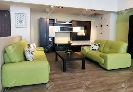 an image of a modern living room with brown table and green