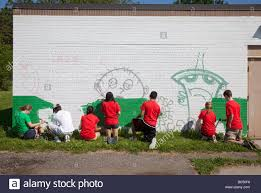 youth volunteers paint mural on building in city park stock photo stock photo youth volunteers paint mural on building in city park