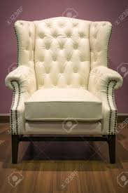 front of classic chesterfield luxury white leather armchair on