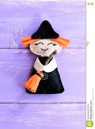 halloween kids background funny felt witch toy isolated on purple wooden background