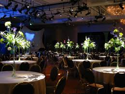 banquet decorating ideas for tables white flowers and green leaves placed on the high glass vases on the