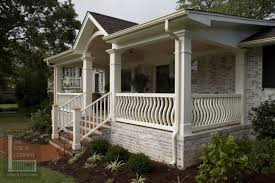 white concrete porch with black metal railing plus beige wall