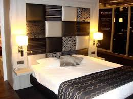 white black bed sheet on the black bed plus white brown wall panel