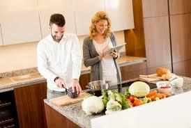 aide de cuisine femme à l aide du comprimé à la table de cuisine tandis que