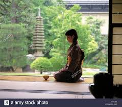 young woman sitting on the porch of japanese style house stock