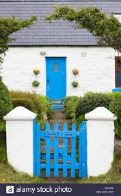 traditional cottage with blue painted wooden front door and gate