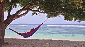 young man with girlfriend relaxing in hammock at tropical beach