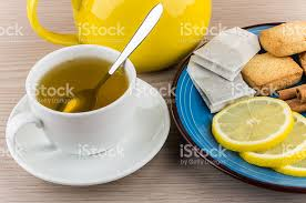 tea and plate with slices of lemon cinnamon and biscuits stock